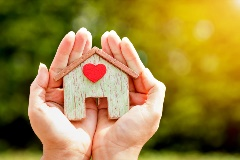Hands holding a house with a heart.