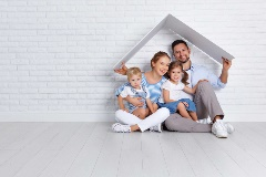 Happy Family sitting under a white abstracted roof shape, in front of a white brick wall.