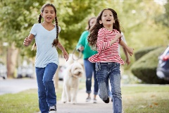 Two young girls run along a city neighborhood sidewalk, followed by their parents and dog.